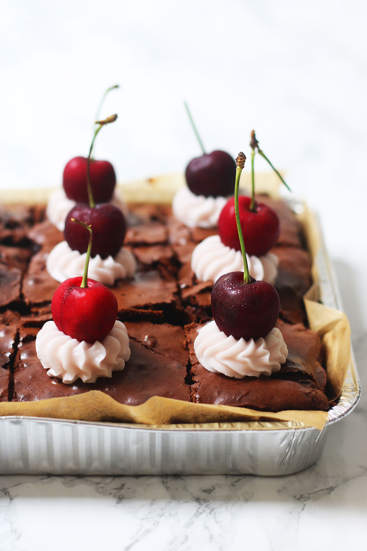 A tray of cherry and pecan brownies topped with cherry buttercream and fresh cherries