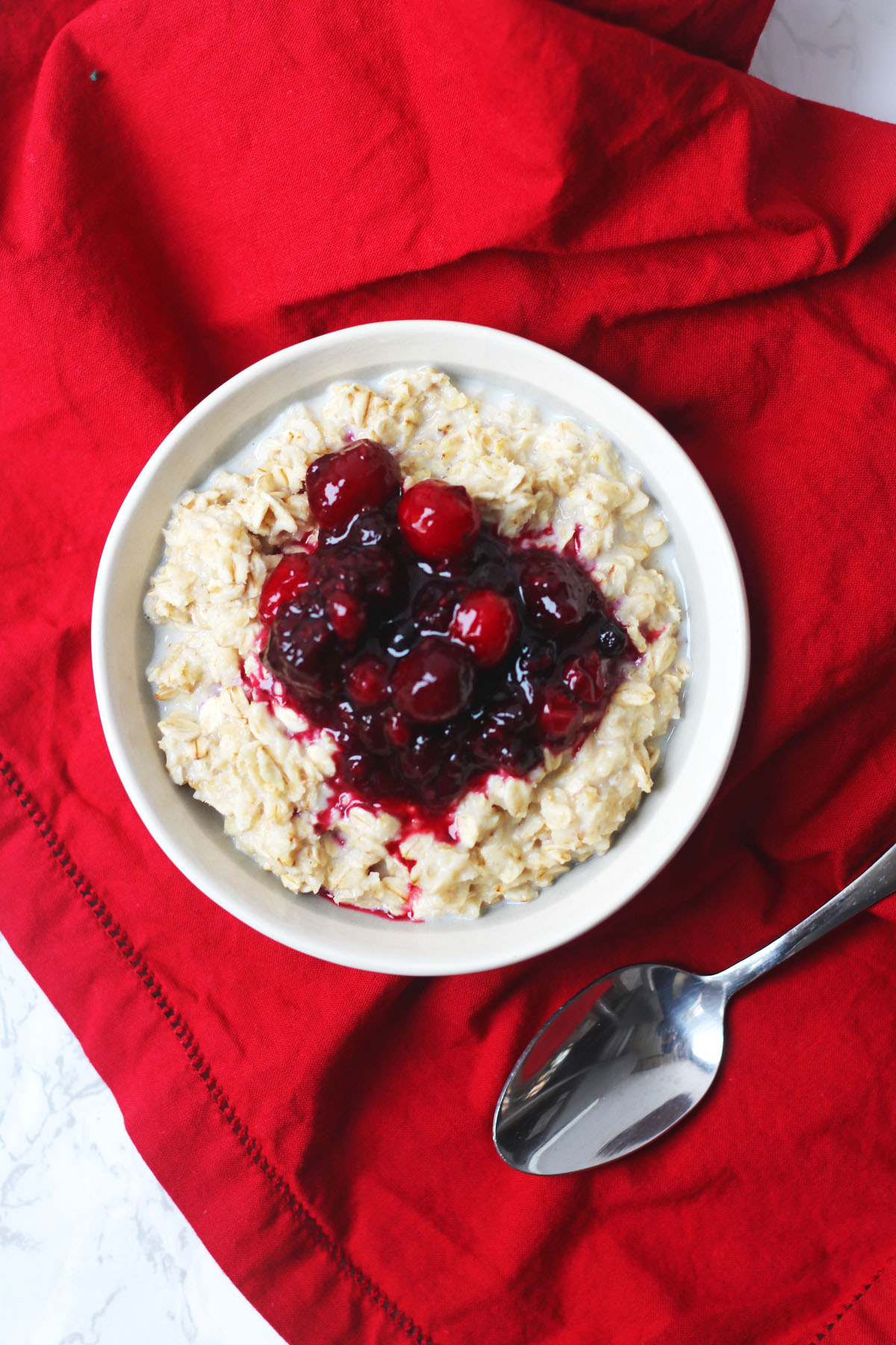 Aerial shot of a bowl of porridge topped with spiced berry compote