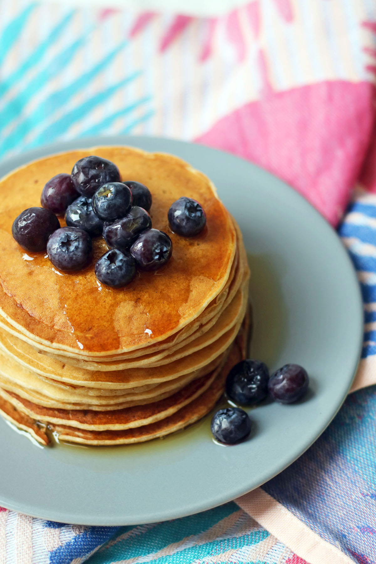 American style vegan pancakes stacked high with maple syrup and blueberries