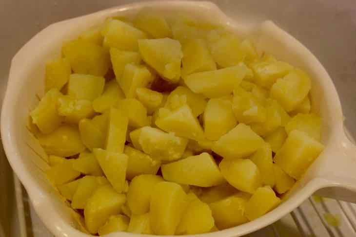 cooked cubed potatoes in a strainer