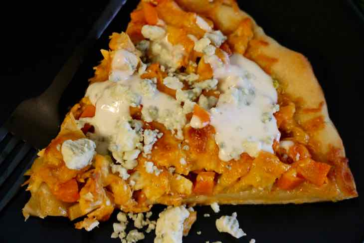 A slice of Buffalo Chicken Wing Pizza Topped with Blue Cheese