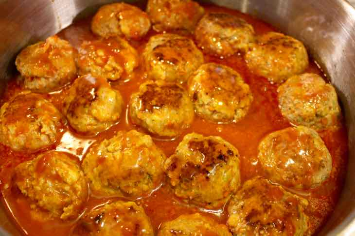 Buffalo Turkey Meatballs in skillet with wing sauce