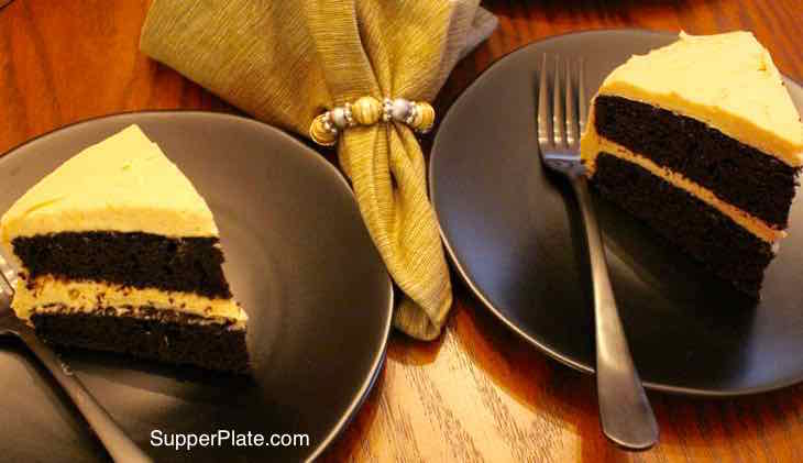 Homemade Chocolate Cake. Two slices on black plates with forks and a green napkin between them