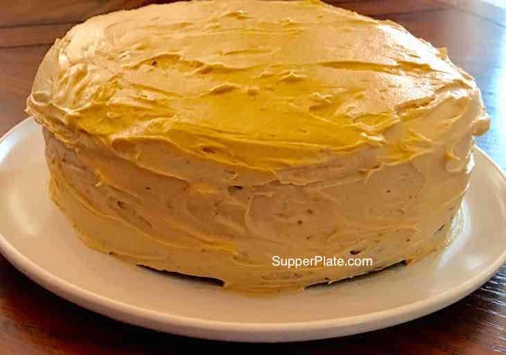 Fluffy Peanut Butter Frosting on a cake on a white plate