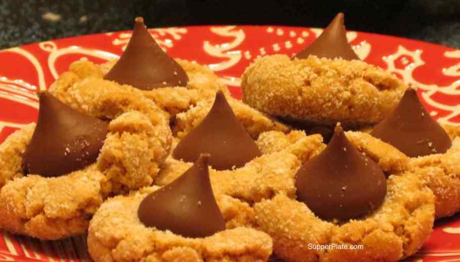 Close up of Peanut butter Blossoms on a red Christmas plate