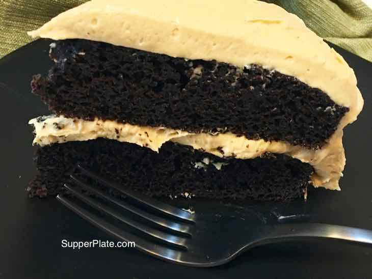 Closeup of Homemade Chocolate Cake with Fluffy Peanut Butter Frosting with a black fork