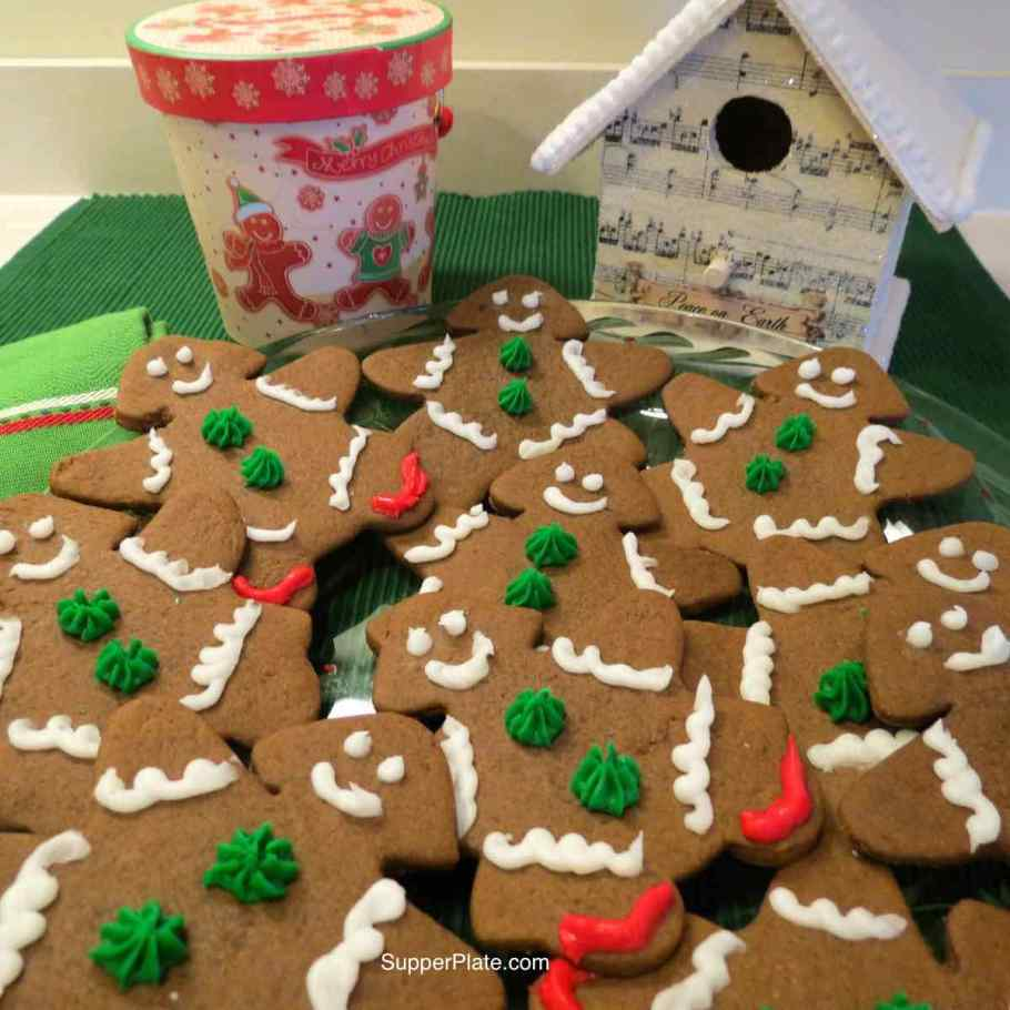Soft Gingerbread Cookies on a green placemat with a Christmas Box and Christmas bird house behind them
