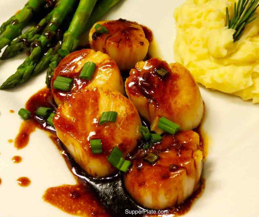 Asian Scallops plated with a side of steamed asparagus and mashed potatoes with a rosemary sprig