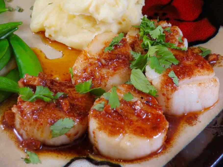 Spicy Scallops plated with spicy sauce drizzled over them with a side of mashed potatoes and snap peas