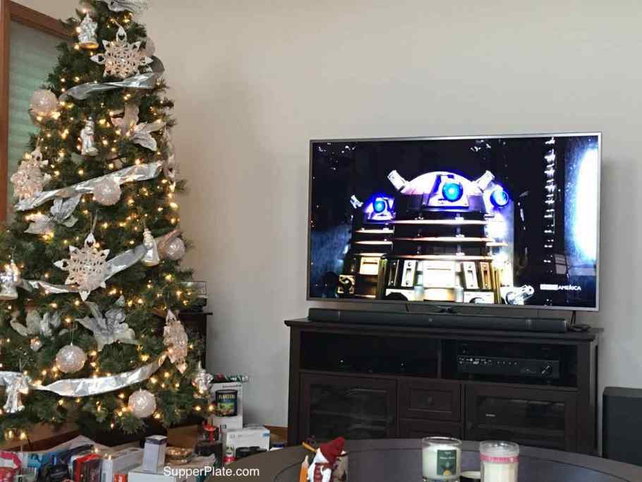Picture of a Christmas tree and a large screen TV with Dr Who Daleks on the screen