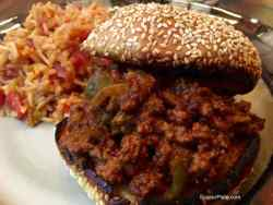 Sloppy Joes served on a toasted roll with a side of Spanish rice on a plate