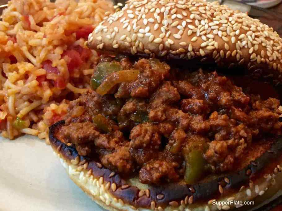 A side view of sloppy joes on a toasted roll with a side of Spanish rice on a plate
