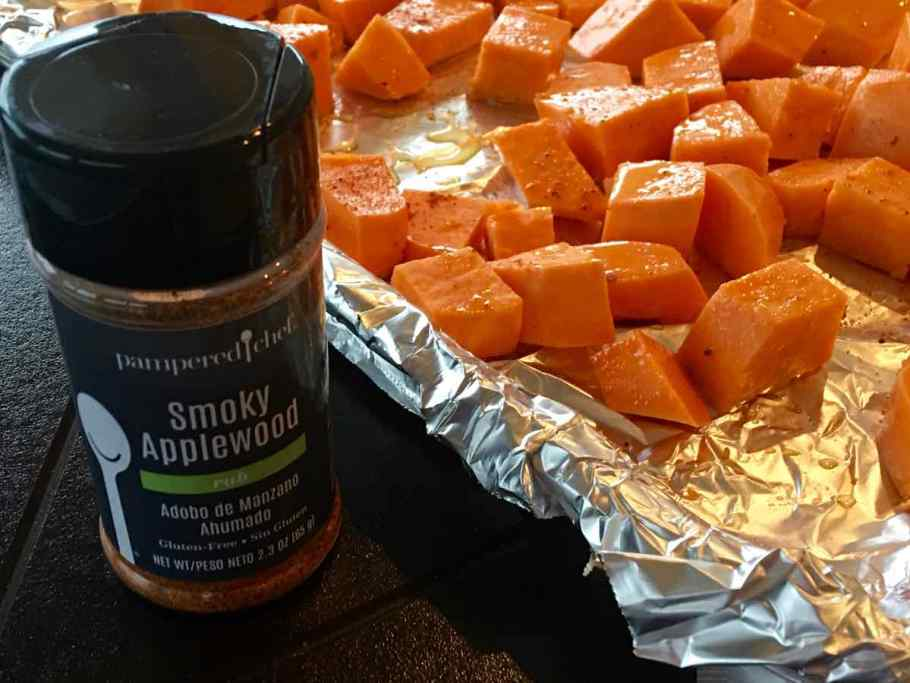 Close up of sweet potatoes on a baking pan with a bottle of Smoky Applewood