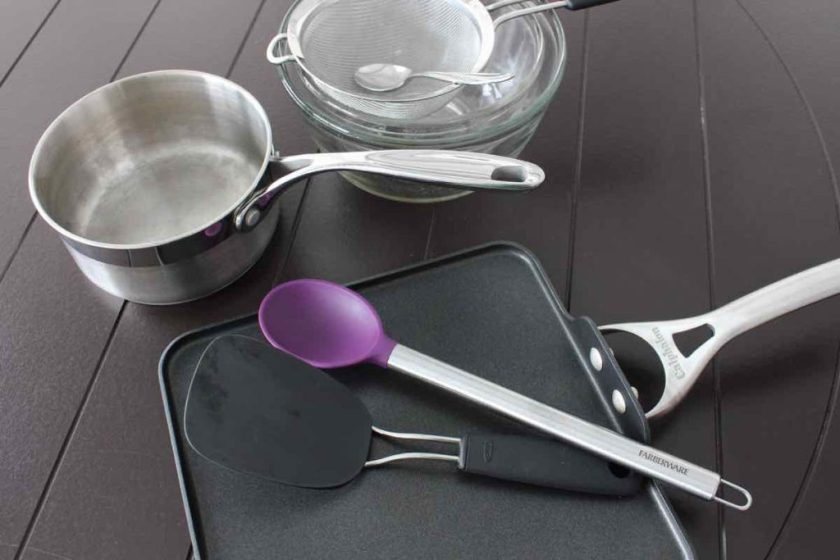 Equipment to make pancakes, griddle and saucepan on a brown table