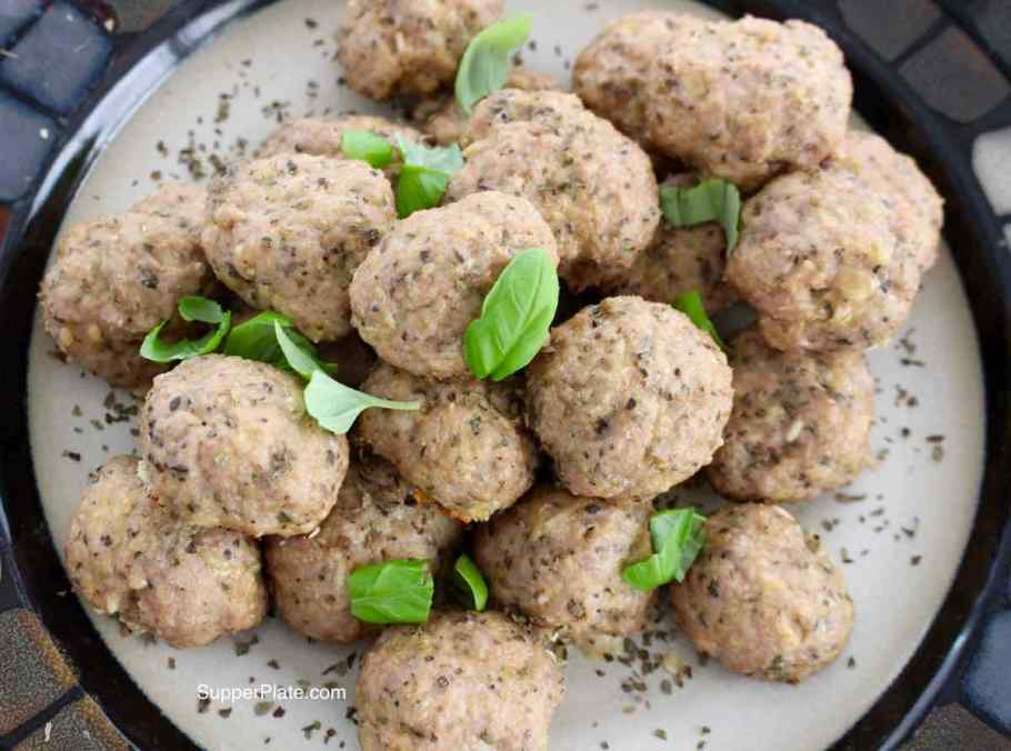 Top View of Baked Mini Turkey Meatballs Closeup picture on a plate topped with fresh basil