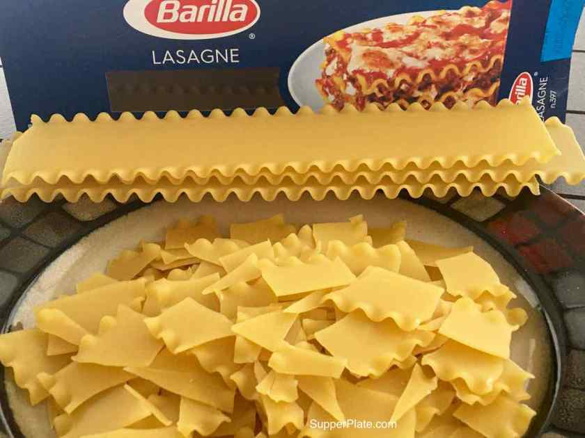 Broken lasagna noodles on a plate with sheets of lasagna noodles and a box of noodles behind them