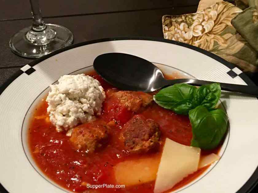 Close up of lasagna soup in a white bowl with a black spoon, green napkin