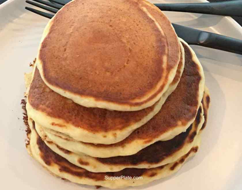 Stack of pancakes on a white plate with black fork.