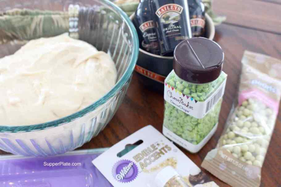Large clear bowl with frosting surrounded by decorative items green napkin and baileys irish cream small bottles