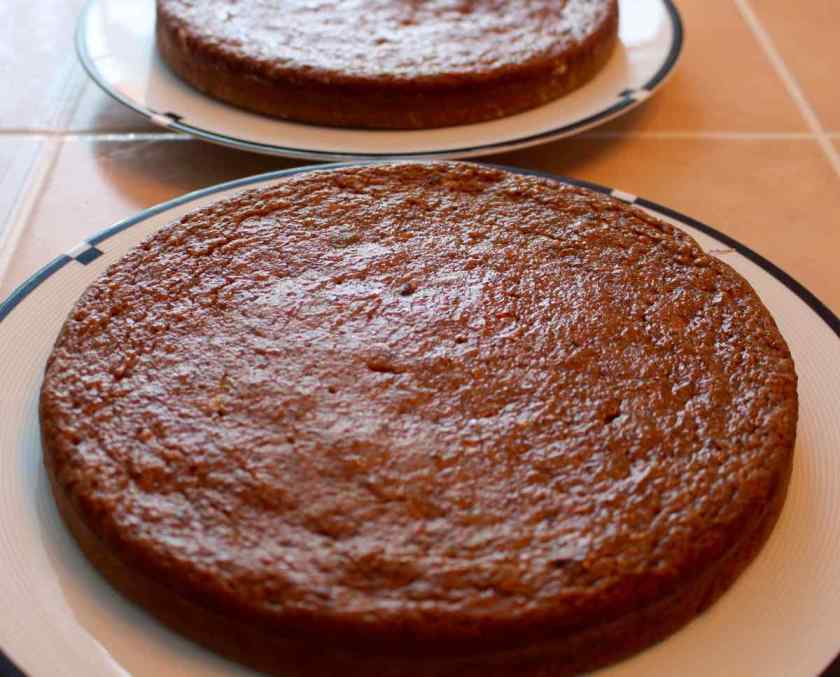 Two cakes out of their cake pans on white plates