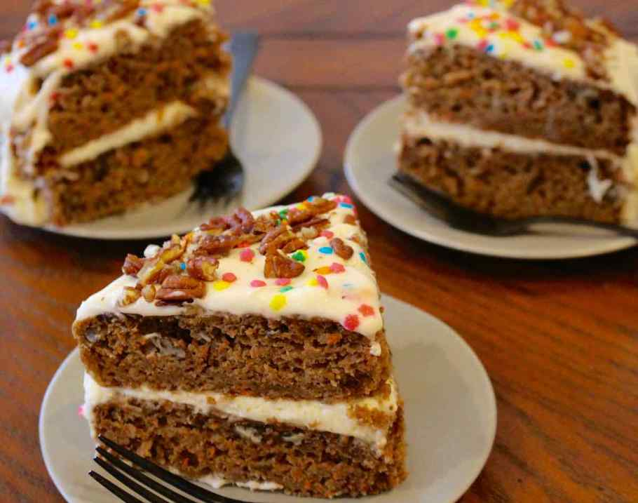 Three slices of Carrot Applesauce Cake on green plates with black forks