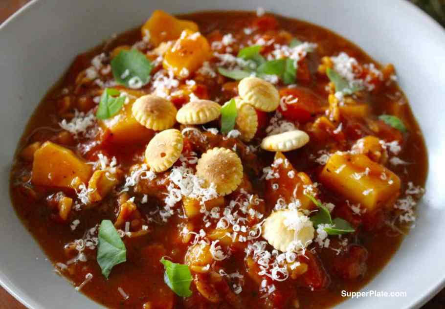 Top view of Beef Minestrone Soup topped with cracker and fresh herbs