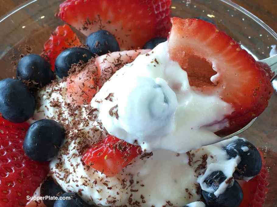 A spoonful of yogurt with berries