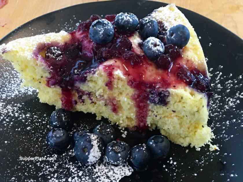 Lemon Blueberry Cake with Blueberry Glaze on a black plate topped with powdered sugar