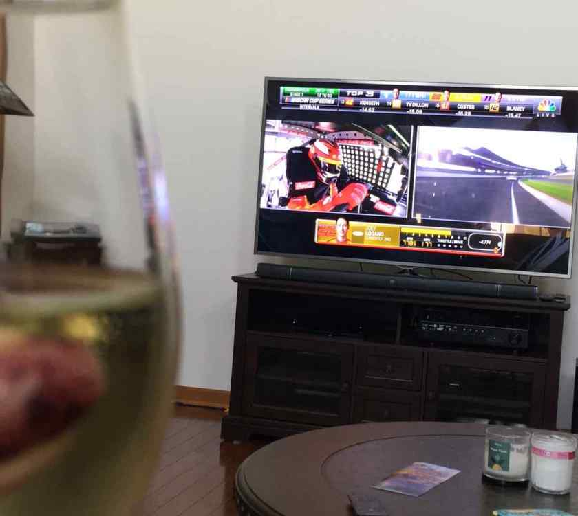 TV with nascar race with wine glass in the foreground