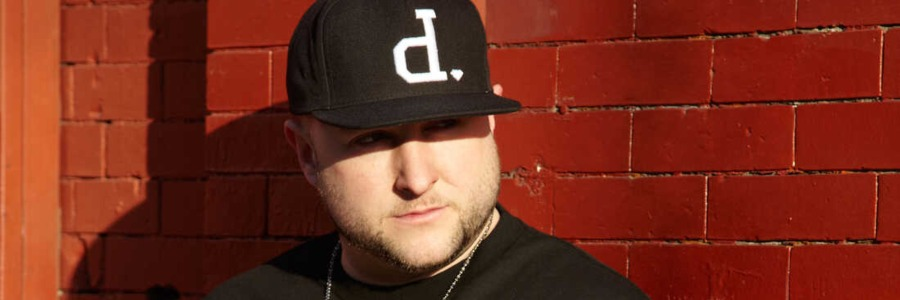 white rapper wearing black t shirt and hat by brick walls