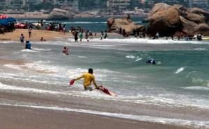 Un salvavidas ayuda a salir del mar a un turista luego de ser arrastrado por el fuerte oleaje en la playa El Morro. Foto: Carlos Alberto Carbajal