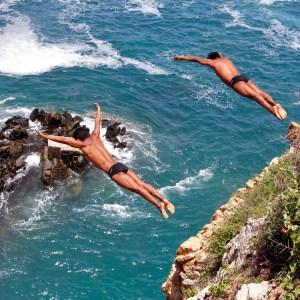 Dos clavadistas se lanzan simultáneamente al mar desde un acantilado en La Quebrada, uno de los sitios turísticos más famosos a nivel mundial en Acapulco. Foto: Carlos Alberto Carbajal