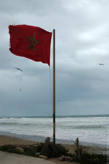 Марокканский флаг на фоне волн, пасмурная погода. Фото сделано из школы серфинга в Марокко Surf-Burg