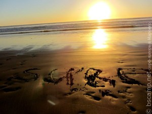 Слово SURF написанное на песке на фоне заката | Школа серфинга в Марокко Surf-Burg