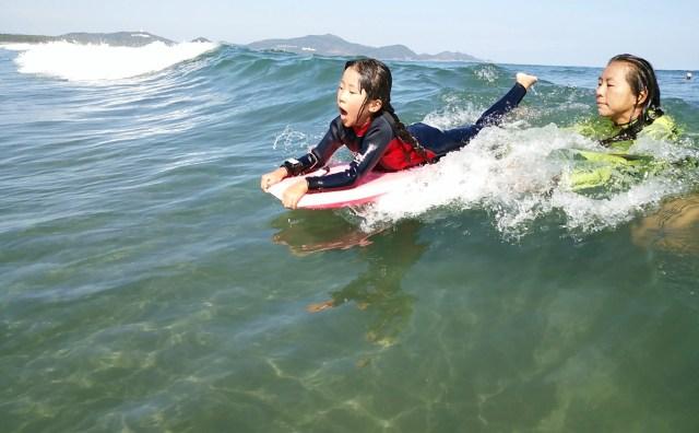 お倉ヶ浜サーフビーチで弘子ママに押してもらい波をキャッチする三村美月ちゃんの写真