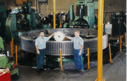 photo of two men in front of a gigantic gear holding a small gear at Industrial Sprockets and Gears