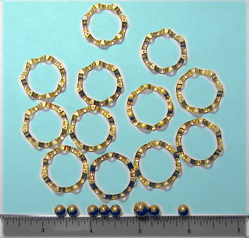 Photo of Twelve Gold Rings and Eight Ball Bearings set against clear ruler for scale treated by Surface Engineering Technologies LLC