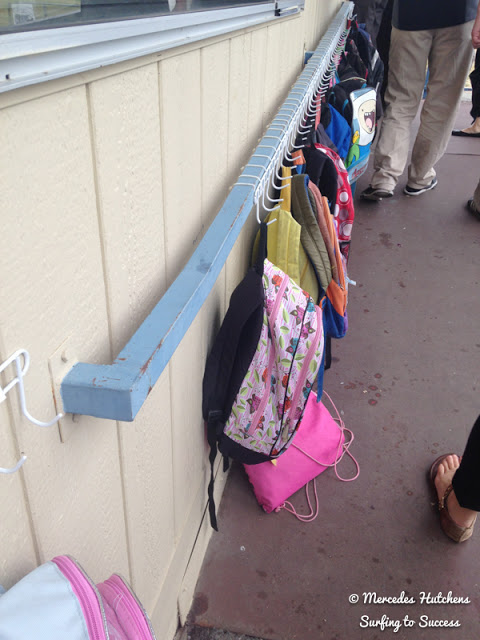 Hang backpacks from rail with plastic hooks. You can use zip ties to secure the hooks to the railing.