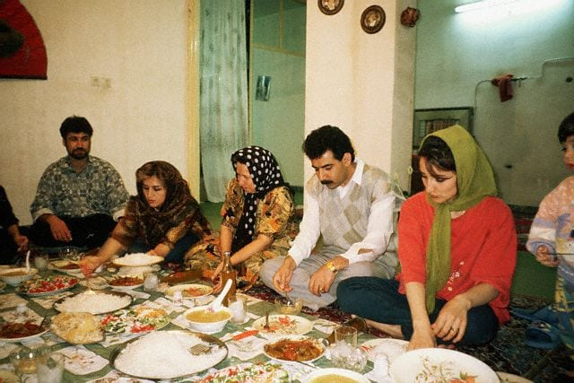 April 1997, Iran --- An Iranian family eats a meal in typical fashion. A carpet is spread onto the floor, the mother and father sit in the middle and the women serve the food. Shiraj, Iran   Location: Shiraj, Iran. --- Image by © Earl & Nazima Kowall/CORBIS