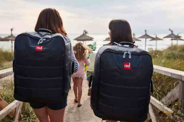 Chicas transportando una tabla de paddle surf hinchable en la mochila.