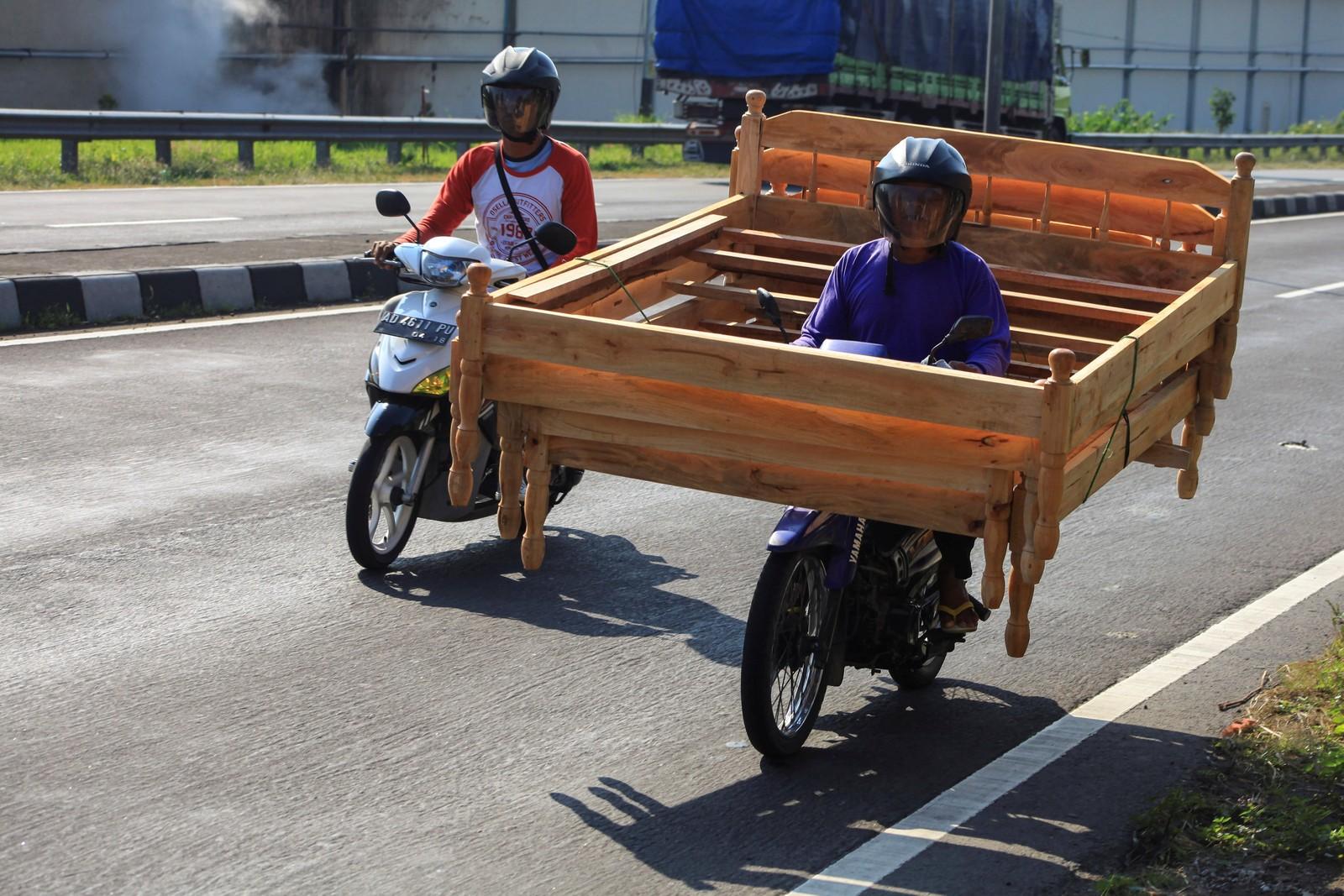 Motociclista leva camas de madeira em moto na Indonésia