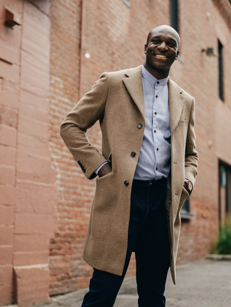 classic beige overcoat with dark jeans and a light blue shirt