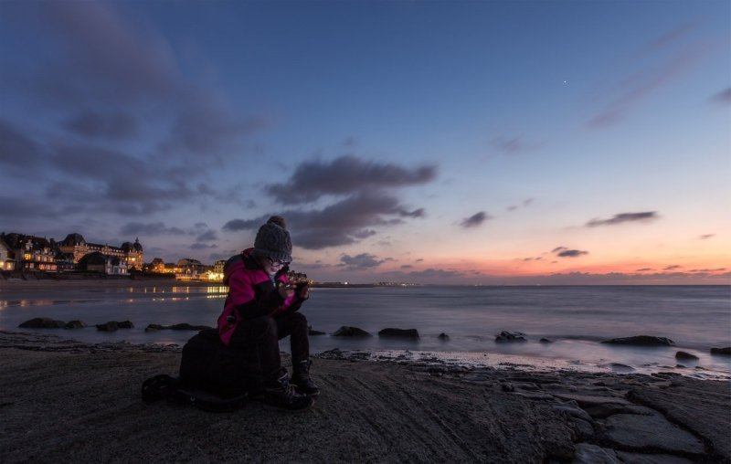 woman alone beach using social media