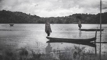 Black and white photo of people standing on canoes