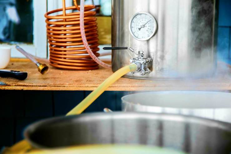Home brewing kit and pouring craft beer wort into the boil kettle with a silicone tube | Home Brewing: Fun Hobby Or Vital Skill?