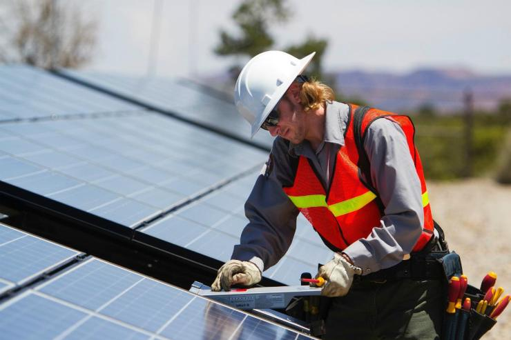Male technician installing battery in blue solar panel | DIY Solar Power - Part 2