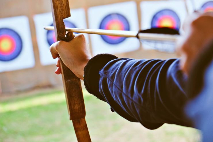Archer holds his bow aiming at a target | Archery 101: Tips And Tricks For Beginners