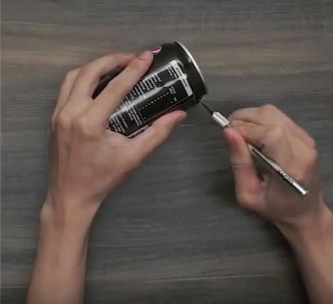 Hands cutting off the top of a Pepsi can with an Exacto knife.