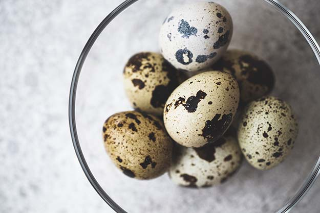 About 7 spotted quail eggs in a clear glass bowl on a gray countertop