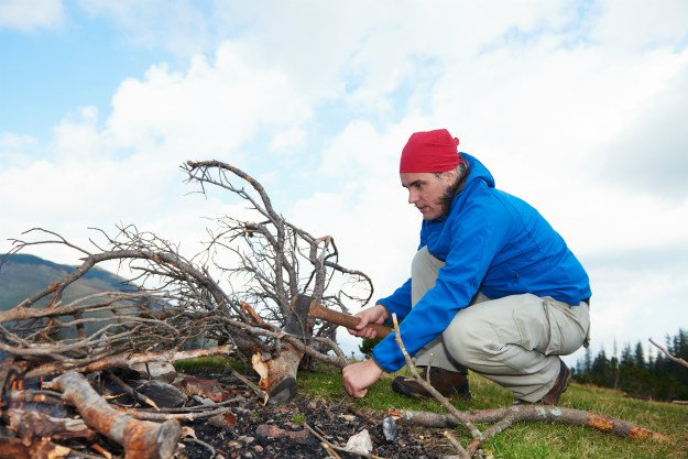man-collecting-fire-wood How To Start and Maintain a Fire in a Winter Survival Situation